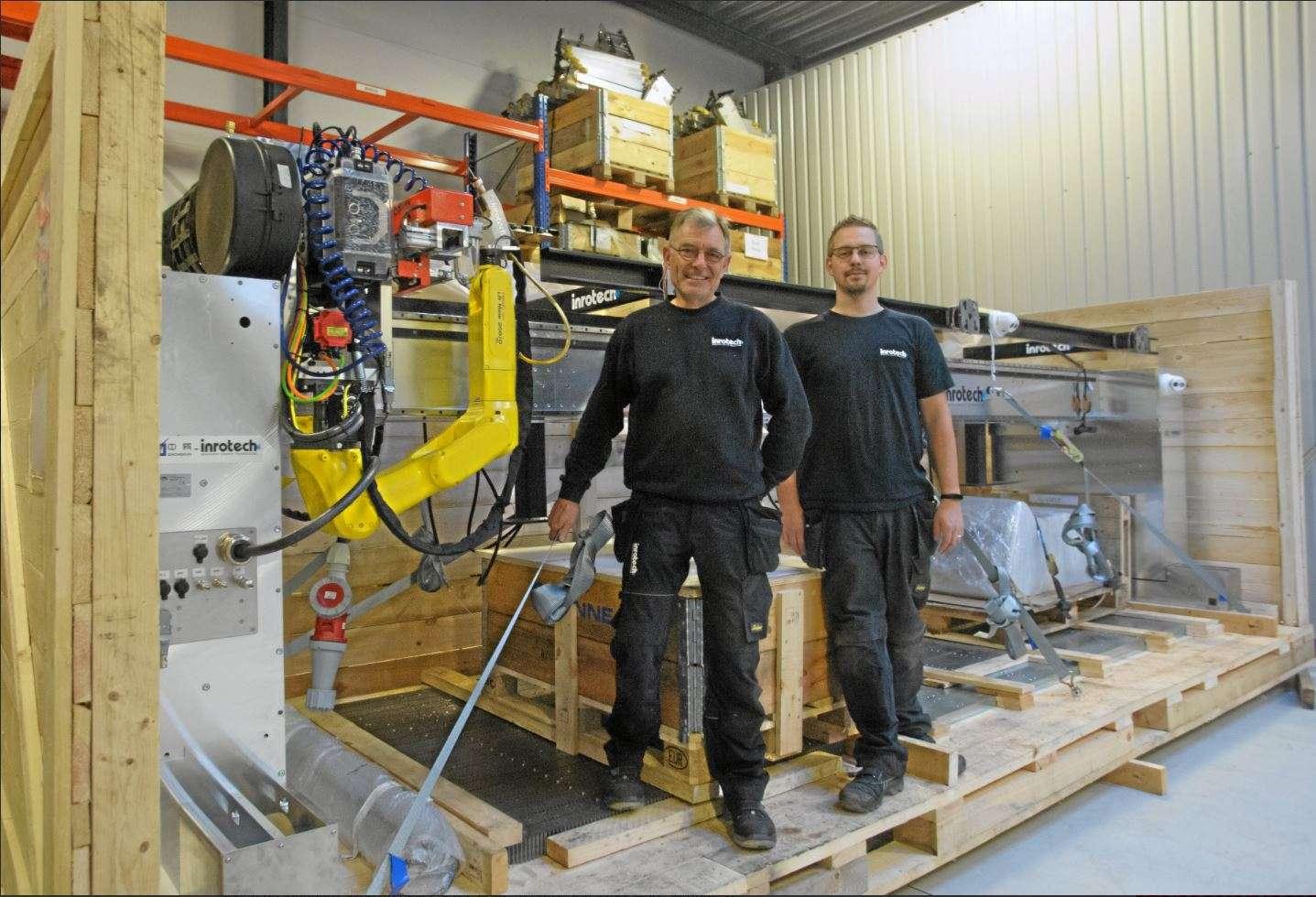 welders in front of welding robot